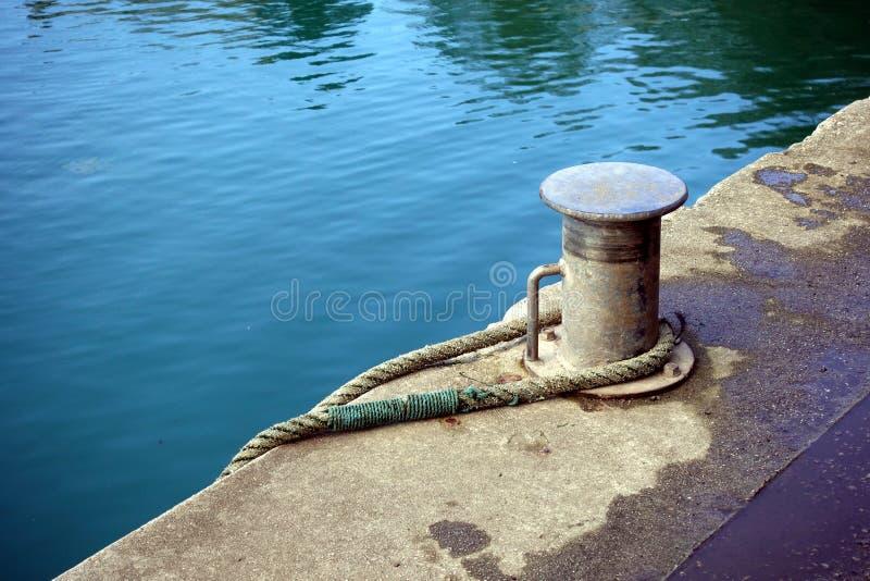 Metal la borne sur un mur de mer de port, avec la corde forte ronde il, images libres de droits