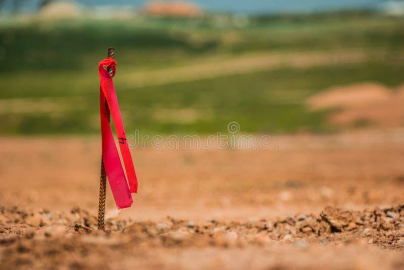 Metal la clavija de la encuesta con la bandera roja en emplazamiento de la obra imagen de archivo