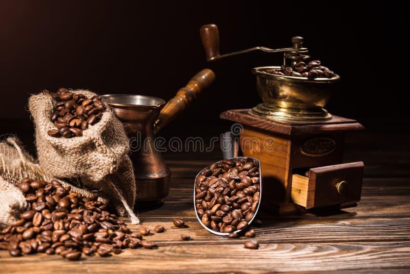 metal la cucharada, el cezve del vintage y la amoladora de café en la tabla de madera rústica derramada foto de archivo libre de regalías
