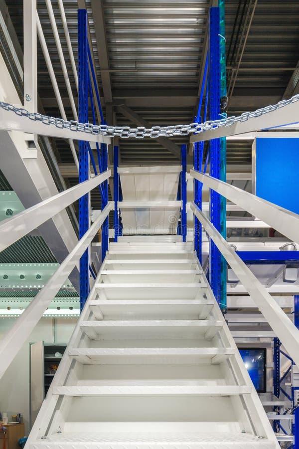Metal la escalera, con las verjas azules y los pasos del metal blanco foto de archivo libre de regalías