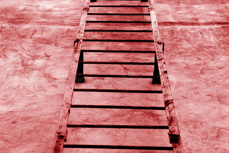 Metal la escalera en la pared del cemento en tono rojo imágenes de archivo libres de regalías