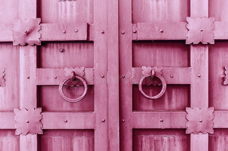 Metal la porta strutturata annata rosa con le maniglie di porta degli anelli ed i dettagli del metallo nella forma di fiori stili fotografia stock libera da diritti