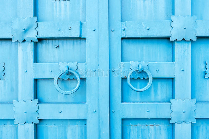 Metal la puerta texturizada envejecida azul con los tiradores de puerta de los anillos y los detalles del metal en la forma de fl imágenes de archivo libres de regalías