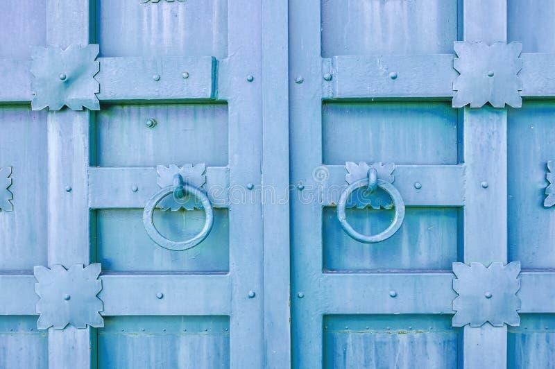 Metal la puerta texturizada envejecida de la violeta pálida con los tiradores de puerta de los anillos y los detalles del metal e foto de archivo libre de regalías