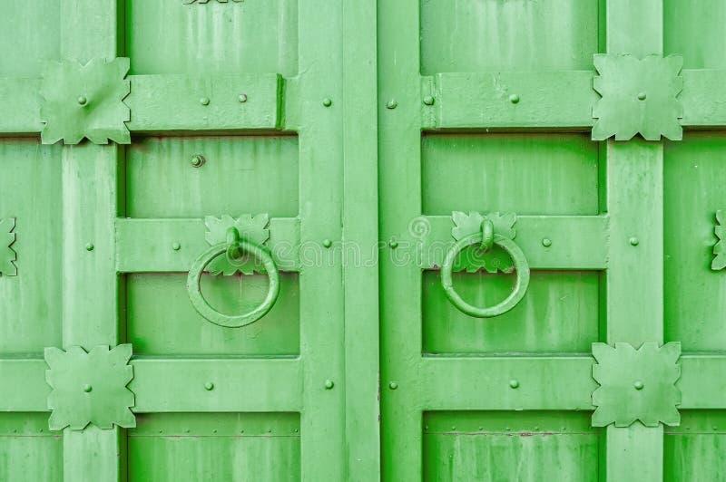 Metal la puerta texturizada envejecida verde con los tiradores de puerta de los anillos y los detalles del metal en la forma de f fotos de archivo