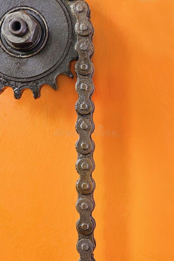 Metal la rueda dentada con la cadena en el primer anaranjado del fondo imagenes de archivo