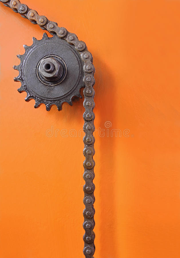 Metal la rueda dentada y la cadena negra en fondo anaranjado fotografía de archivo