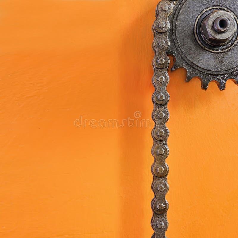 Metal la rueda dentada y la cadena negra en fondo anaranjado con el espacio vacío foto de archivo libre de regalías
