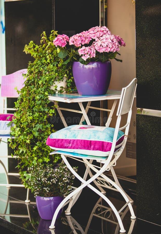 Metal la silla, la tabla del jardín y las plantas en potes fotos de archivo libres de regalías