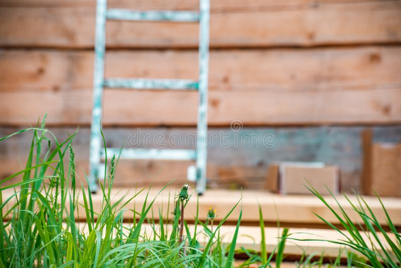 Metal ladder at a construction site of a wooden house and green grass. Soft focus, home, industry, equipment, exterior, roof, structure, outdoor, build royalty free stock photos