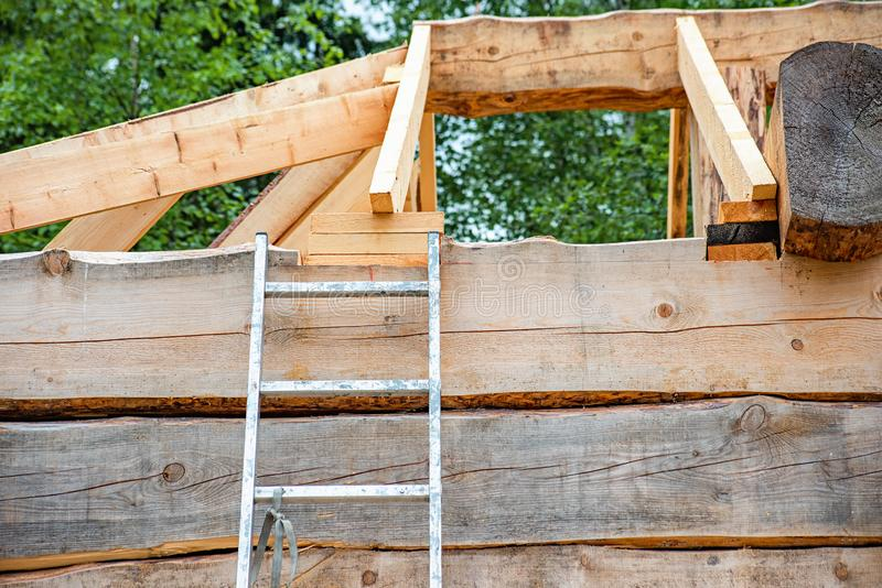 Metal ladder at a construction site of a wooden house. Soft focus, home, industry, equipment, exterior, roof, structure, outdoor, build, occupation, building stock photo