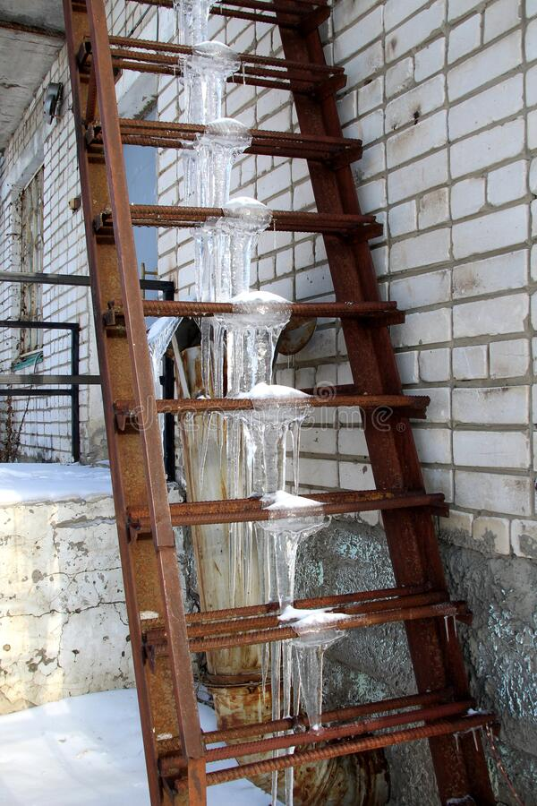 Ice icicles formed on the iron stairs. Metal, ladder, icing, ice, icicle, climate, cold, danger, hang, frozen, hang, house, icy, long, many, natural, nature, old royalty free stock photography
