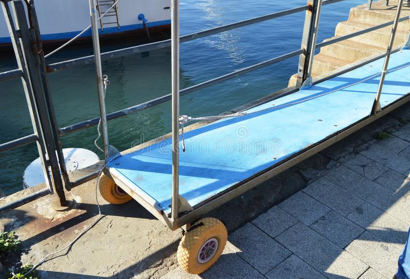 Metal ladder with wheels, for the safety of passengers, between the pier and the ship in the port royalty free stock image