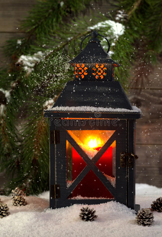 Metal Lantern with Glowing Candle during the holiday season. Vertical front view of an old metal lantern, glowing red candle inside, with falling snow and an stock photography