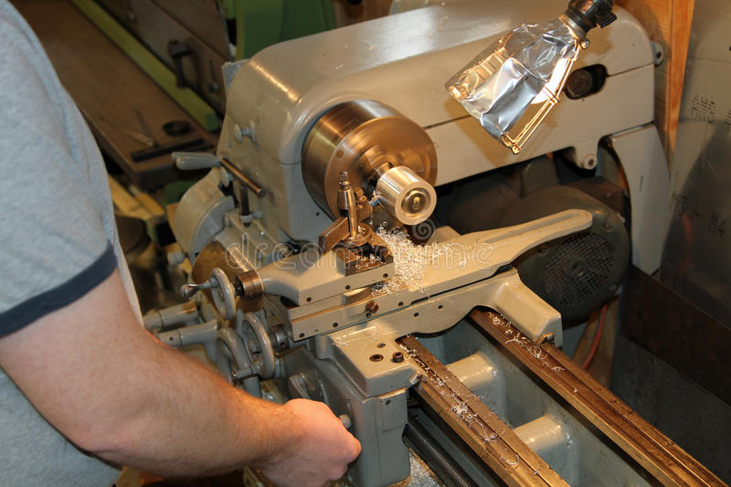 Metal lathe worker. Man works turning down aluminum part on a metal lathe stock photography