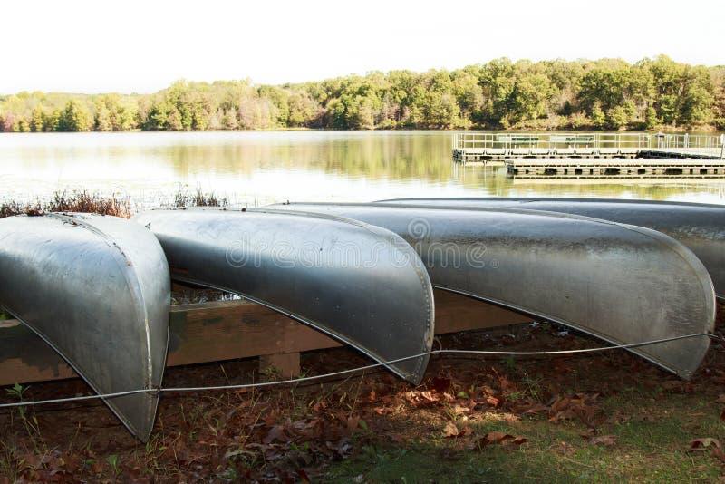Metal le canoe che riposano su uno scaffale della barca vicino al lago immagine stock