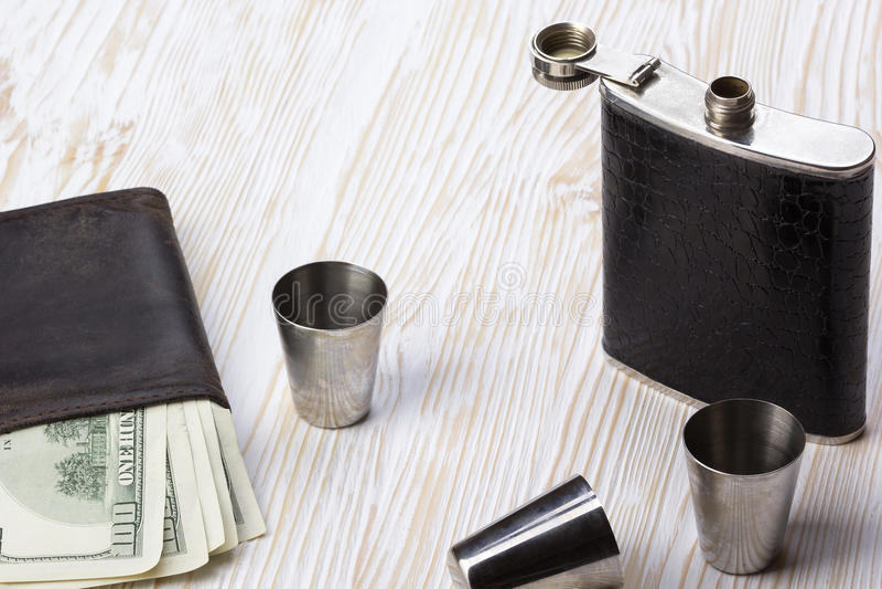 Metal le cuir équilibré par flacon, trois verres à liqueur métalliques et le portefeuille photographie stock