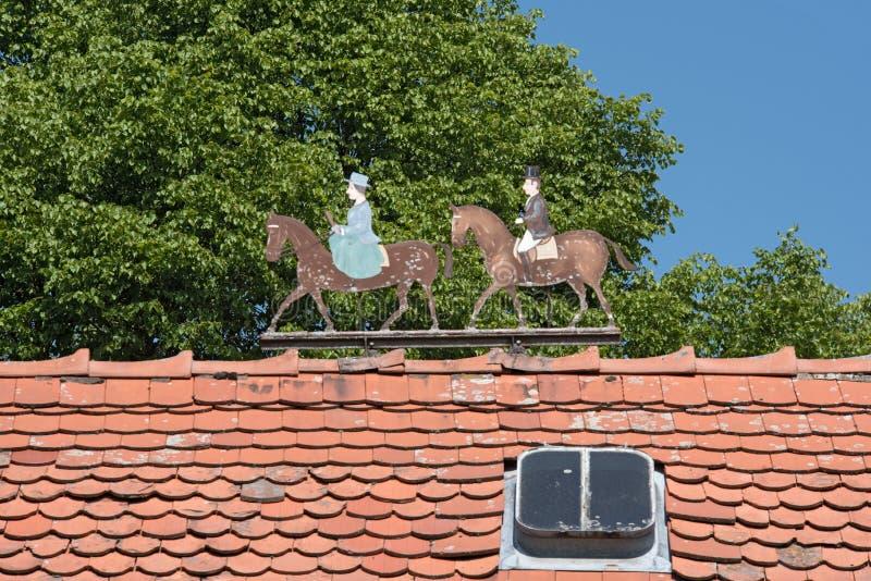 Metal le figure due cavalieri, uomo e donna sul tetto di una proprietà fotografia stock