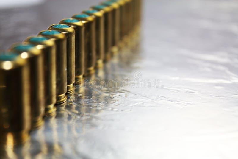 Metal le munizioni dei hub della pistola sullo scrittorio d'argento brillante fotografia stock