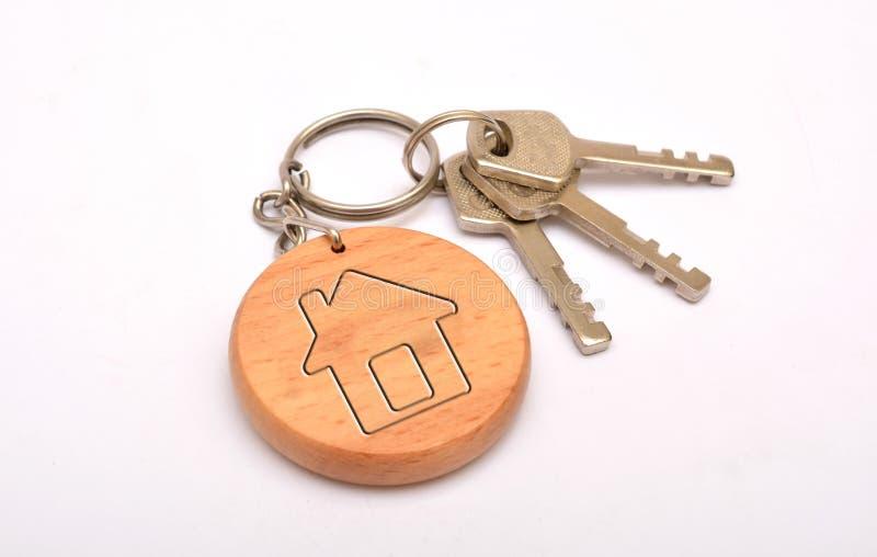 Metal les clés de porte avec le porte-clés de maison-forme d'isolement sur le fond blanc photos stock
