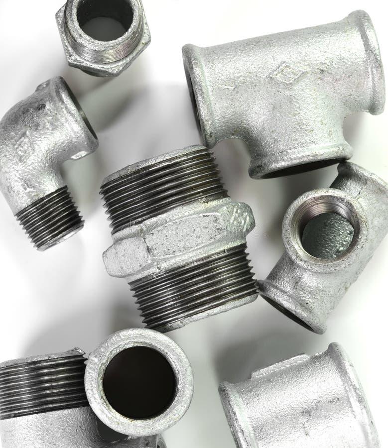 Metal les ferrures de coude pour des tuyaux, fond blanc d'isolement Outils et matériaux pour les travaux sanitaires photo stock