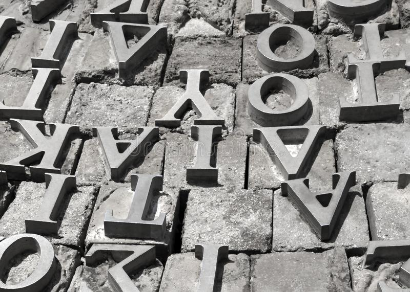 Metal letters of the Greek alphabet on a gray stone surface background stock image