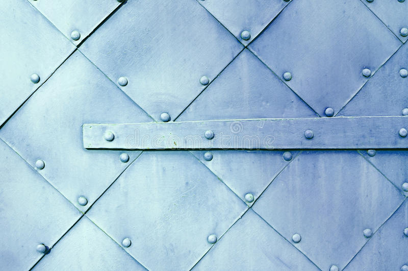 Metal light violet surface of old hammered metal plates with rivets and architectural details on them. stock photography