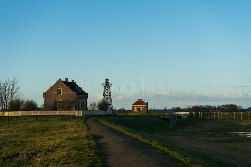 Metal lighthouse tower nex to landhouse leading path blue sky no clouds. Green grass. royalty free stock photography