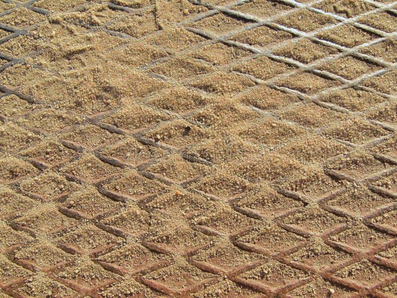 Metal lo strato arrugginito con la terra della parte posteriore della ruggine, grata d'acciaio sulla terra immagine stock libera da diritti