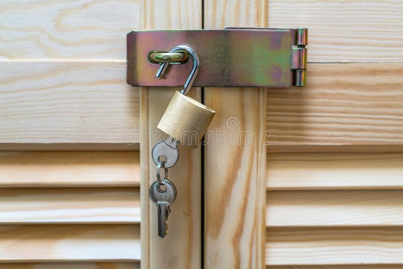 Metal lock with keys hanging on modern wooden cabinet with strips in classic rustic style. Locker wardrobe closet with shutter. Plank doors royalty free stock image