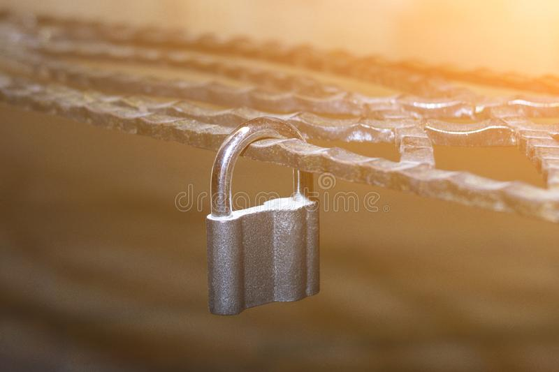 Metal lock, latched on a metal decorative forged lattice. Concept stock image