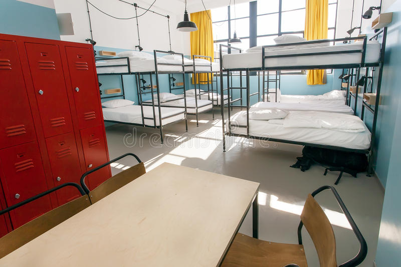 Metal locker, table and double-decker beds inside hostel room with tall windows.  royalty free stock images