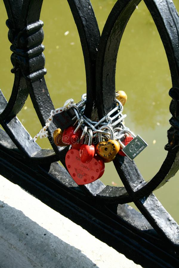 Love locks at a chain in a bridge above a river. Metal locks at a chain in a bridge above a river which couples left as a sign of love and friendship, also being royalty free stock photos