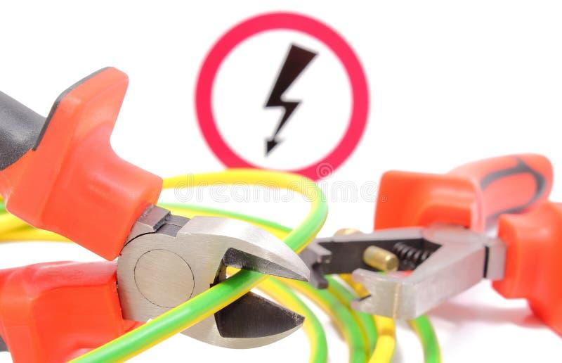 Metal los alicates, el cable amarillo verde y la muestra del peligro del alto voltaje foto de archivo