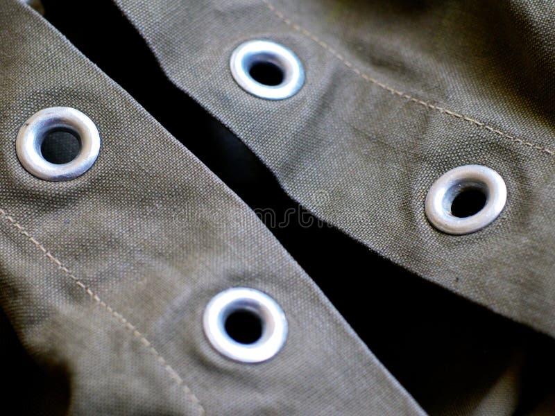 Metal los ojos del rizo del remache en lona verde pesada imagenes de archivo