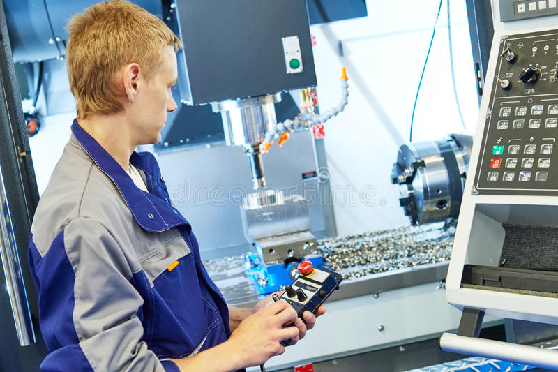 Metal machining industry. Worker operating cnc milling machine stock image
