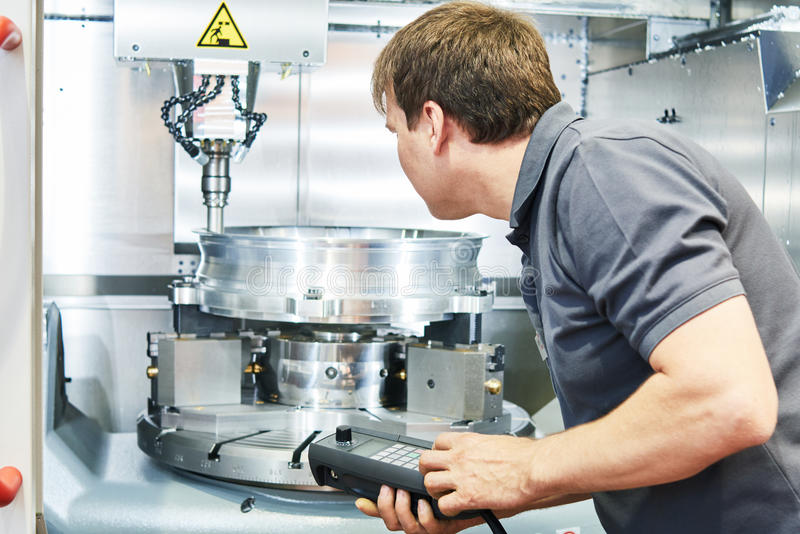 Metal machining industry. Worker operating cnc milling machine. Metal machining industry. Worker or service engineer operating cnc milling machine at factory royalty free stock photos
