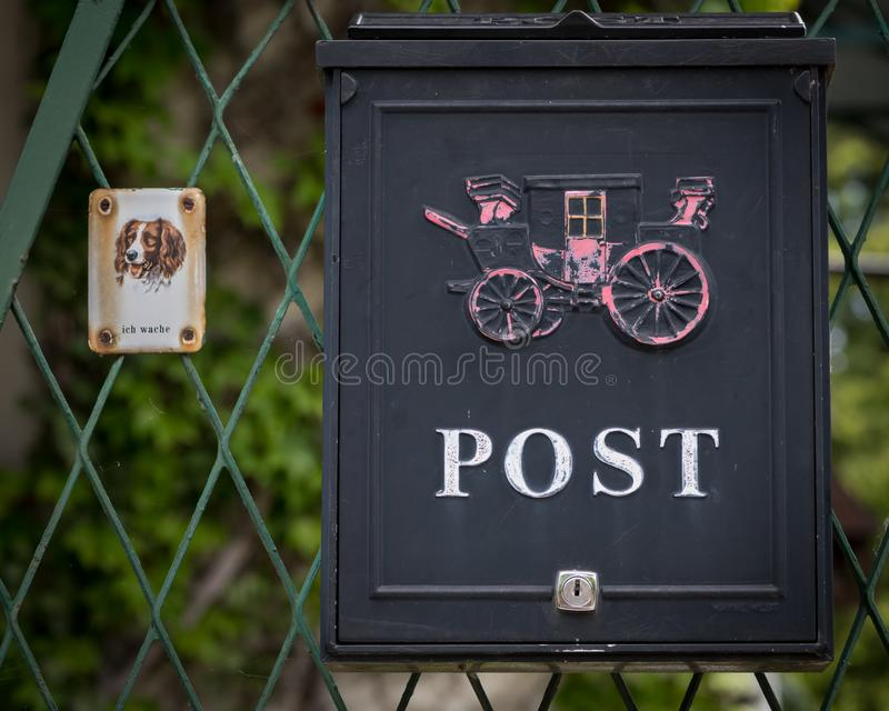 Metal mailbox and sign with dog saying royalty free stock image