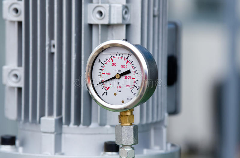 Metal manometer. Close up of metal manometer with machinery in background stock photo