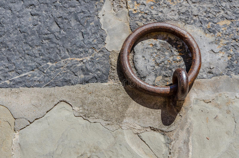 Metal marooning ring on stone ground. Symbolic metal mooring ring on a stone ground of the wharf stock image