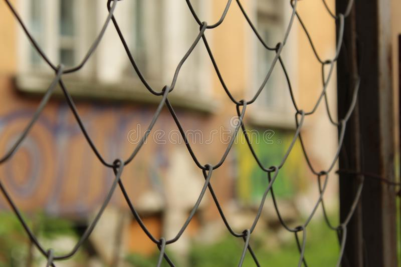 Metal Mesh Fence Fragment Foreground And Graffiti Wall Background City Sofia Bulgaria. Metal Mesh Fence Fragment Foreground And Graffiti Wall Background Sofia royalty free stock photography