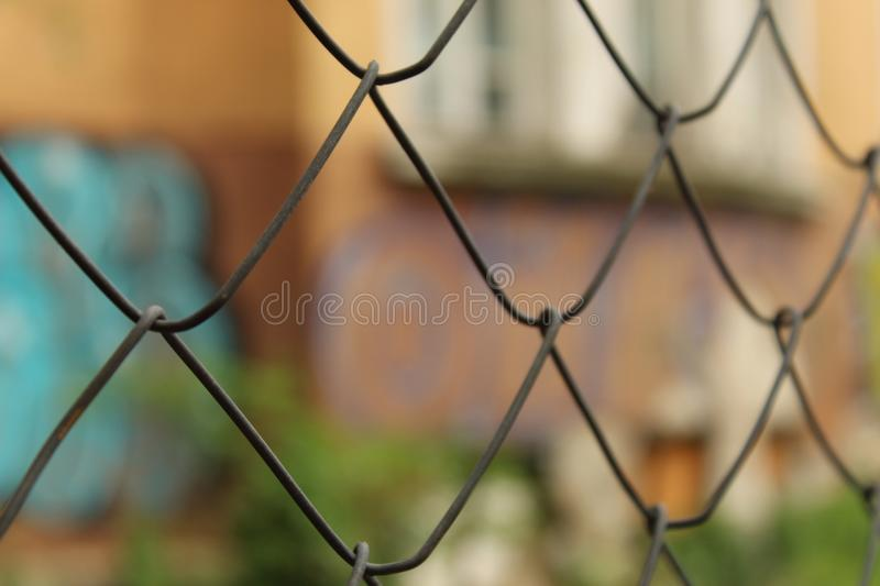 Metal Mesh Fence Fragment Foreground And Graffiti Wall Background City Sofia Bulgaria. Metal Mesh Fence Fragment Foreground And Graffiti Wall Background Sofia stock photography