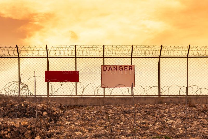 Metal mesh wall with barbed wires security fence and danger notice board on sunset stock image