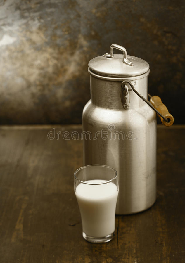 Metal milk can with glass of fresh milk. Metal milk can with a glass of fresh milk standing together on an old rustic wooden table in front of a grungy stained royalty free stock photos
