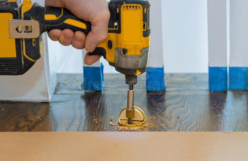 Metal modern professional installing door stopper on wooden floor. In using screwdriver, installation, stainless, design, home, apartment, house, object royalty free stock photography
