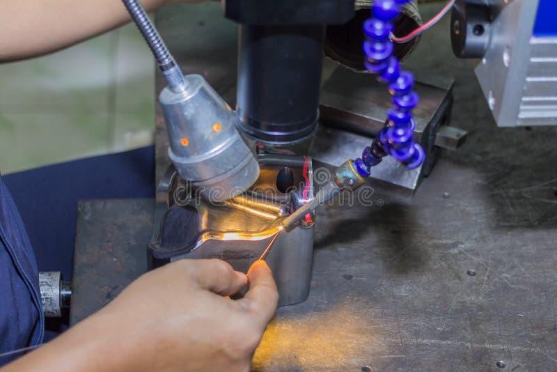 Metal mold and die part repair by welder with laser welding method.  stock photo