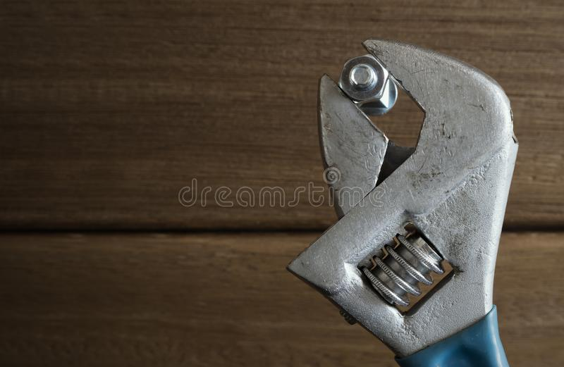 Monkey wrench with and nut on wood background royalty free stock images