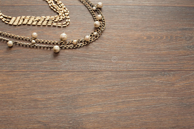 Metal necklace for women on brown wooden background. stock photography