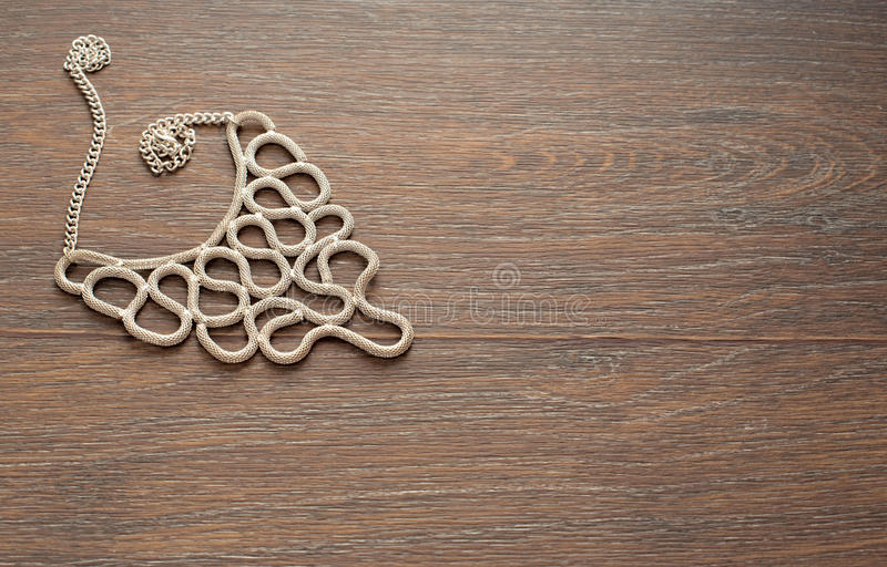 Metal necklace for women on brown wooden background. stock images