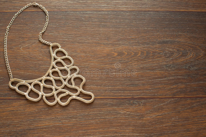 Metal necklace for women on brown wooden background. royalty free stock photography